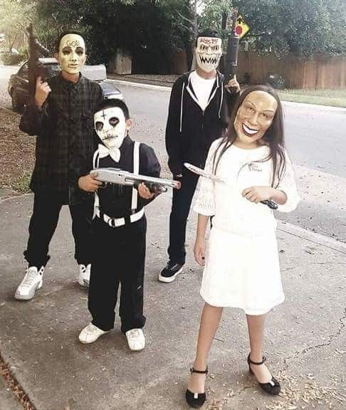 group of kids wearing purge costumes